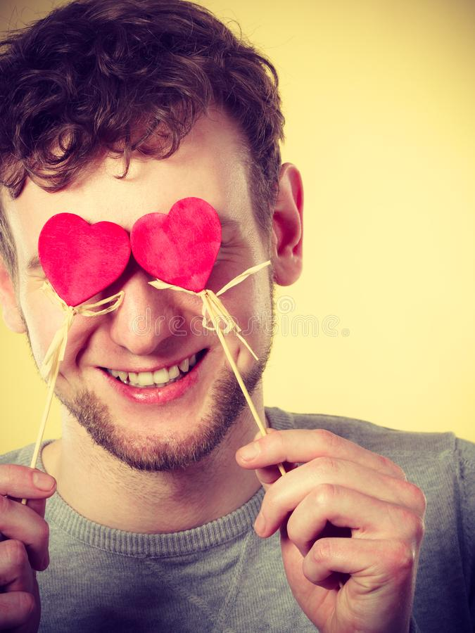 Man blinded by love. Love romance concept. Man blinded by love. Young male holding hearts on sticks before his eyes royalty free stock photography