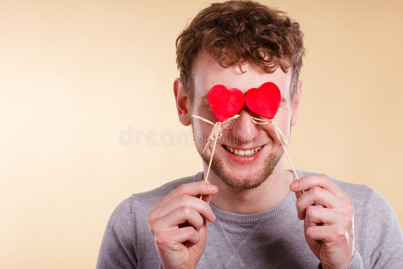 Man blinded by love. Love romance concept. Man blinded by love. Young male holding hearts on sticks before his eyes stock image