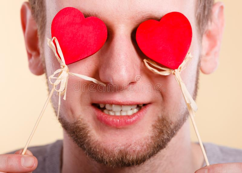 Man blinded by love. Love romance concept. Man blinded by love. Young male holding hearts on sticks before his eyes stock photography