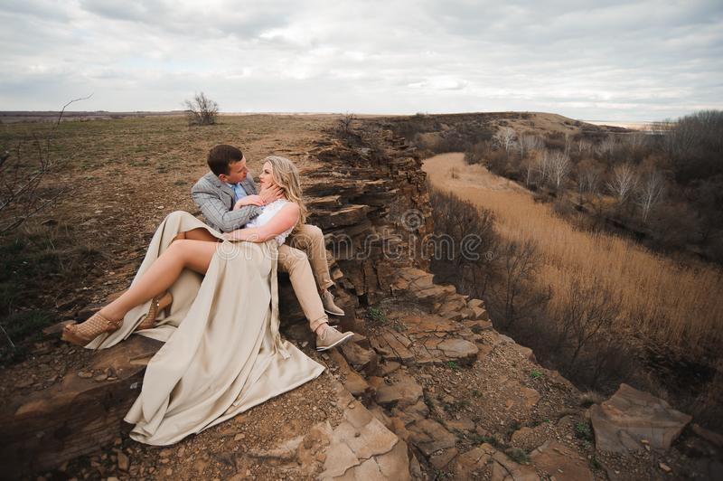 Love, romance and people concept - happy young couple hugging sitting on the edge of a cliff outdoors. stock photo