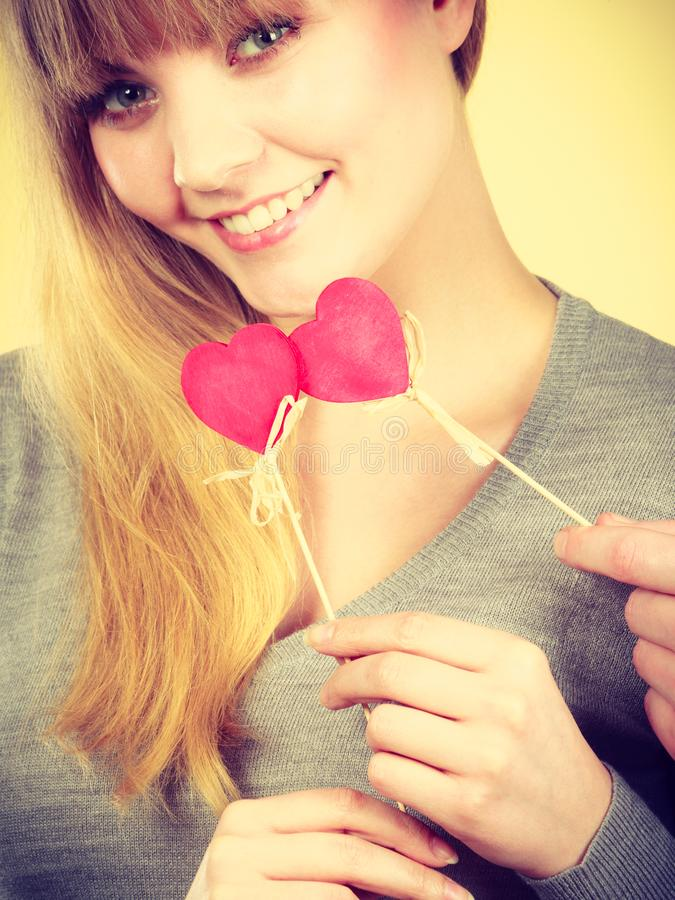 Smiling girl holding hearts. Love romance symbolism concept. Smiling girl holding hearts. Young woman with item on stick stock images