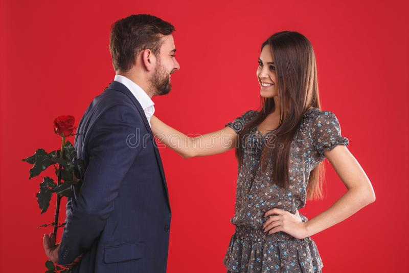 Love, romance, valentines day, couple and people concept - happy young man giving red flower to smiling woman. royalty free stock images