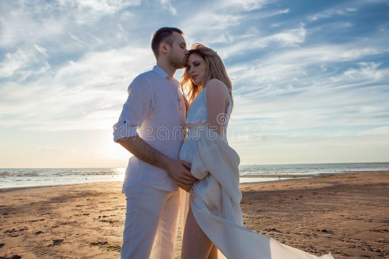 Love, romance, walk. Airy portrait of beautiful couple kissing on background of sunset sea, sandy beach and clouds. royalty free stock image