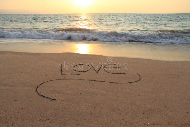 Love in the sand. The word Love, handwritten in a sandy beach at sunset royalty free stock photography