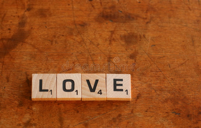 Love. Scrabble letters spelling love on wood surface royalty free stock images