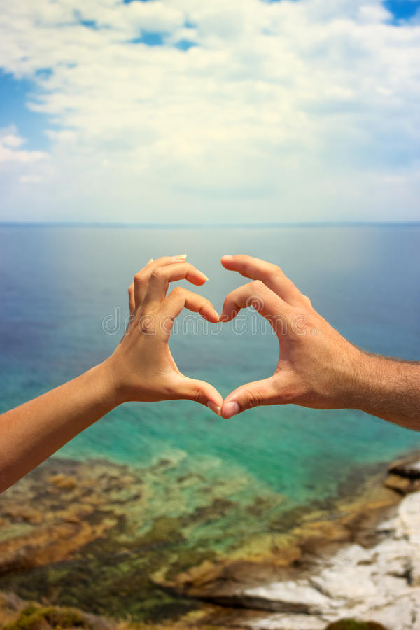 Love and the sea. Couple hands in the heart sign, love and the sea royalty free stock images