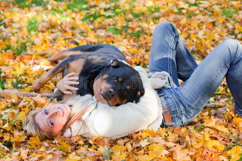 Love and shelter. Woman and her dog laying on golden maple leaves outside on a cold autumn afternoon