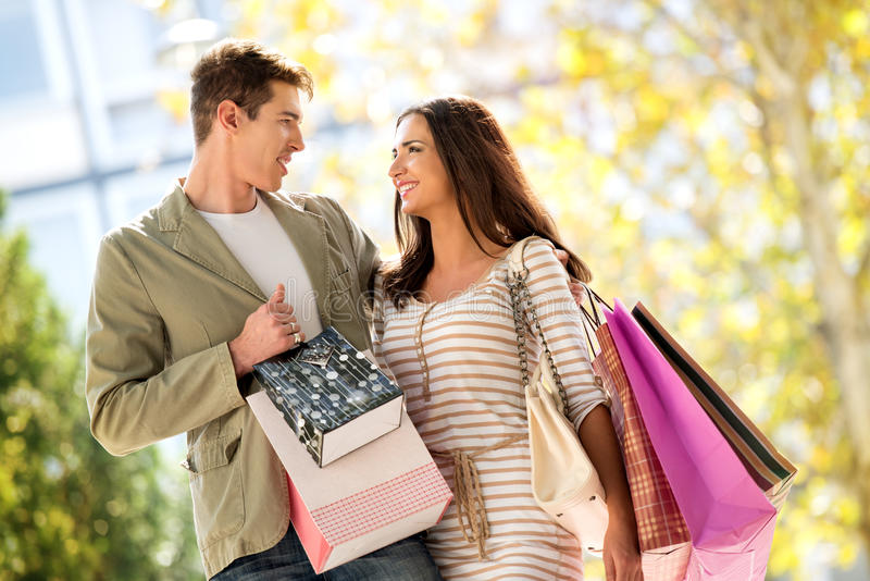 We Love Shopping. Close-up of a beautiful couple in love walking happily through town after shopping, hugging and carrying shopping bags in their hands royalty free stock photos