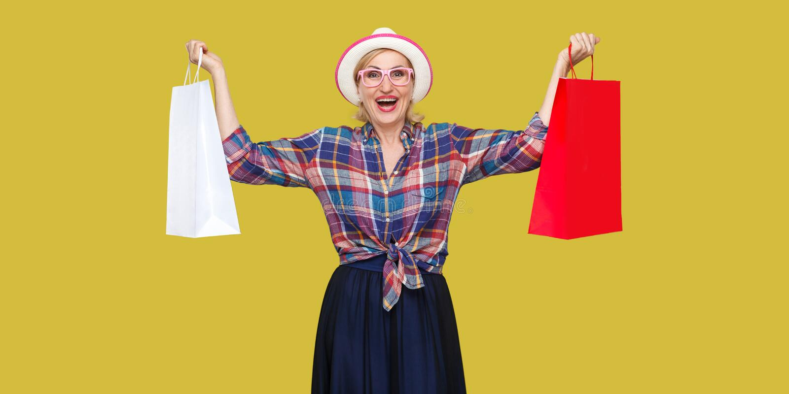 Love shopping! Satisfied modern grandma in white hat and in checkered shirt holding shopping bags and triumphing with raised arms royalty free stock images