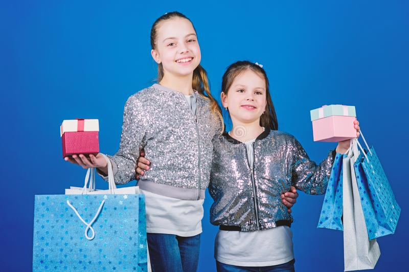 We love shopping. Small girls with shopping bags. Sisterhood. Holiday purchases. Kid fashion. shop assistant with. Package. Sales and discounts. Happy children stock photos