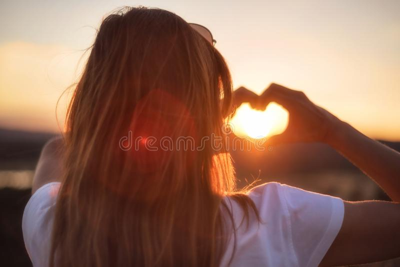 Love sign. Woman making heart with her hands at sunset. stock photos