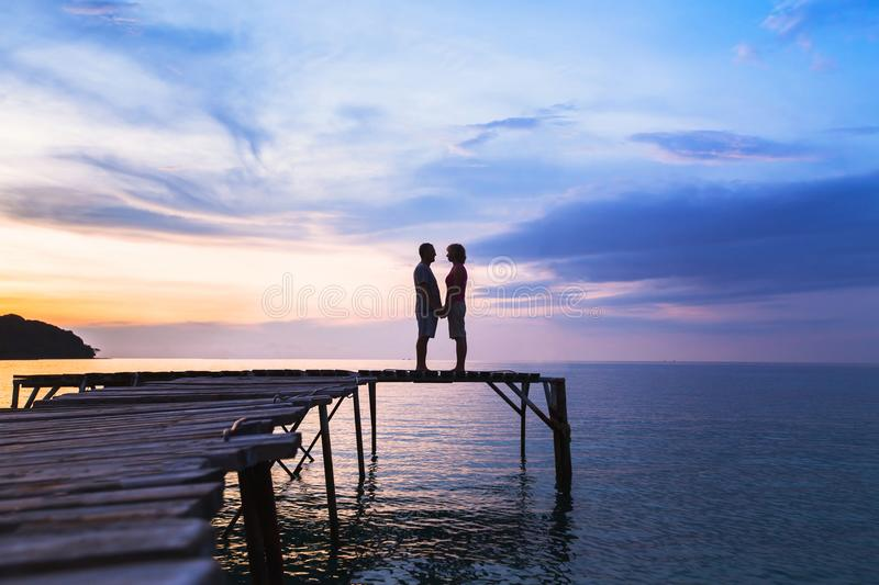 Love, silhouette of affectionate couple on the pier at sunset beach royalty free stock photos