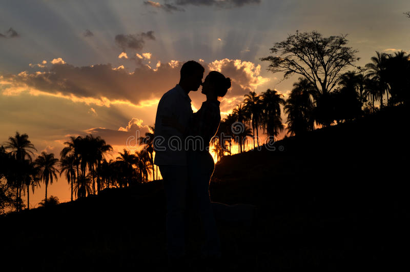 Love in silhouette. Couple loving themselves at sunset royalty free stock photo