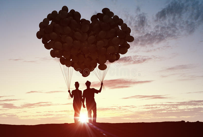 We are in love. Silhouettes of guy and girl representing love and affection on sunset background royalty free stock photography