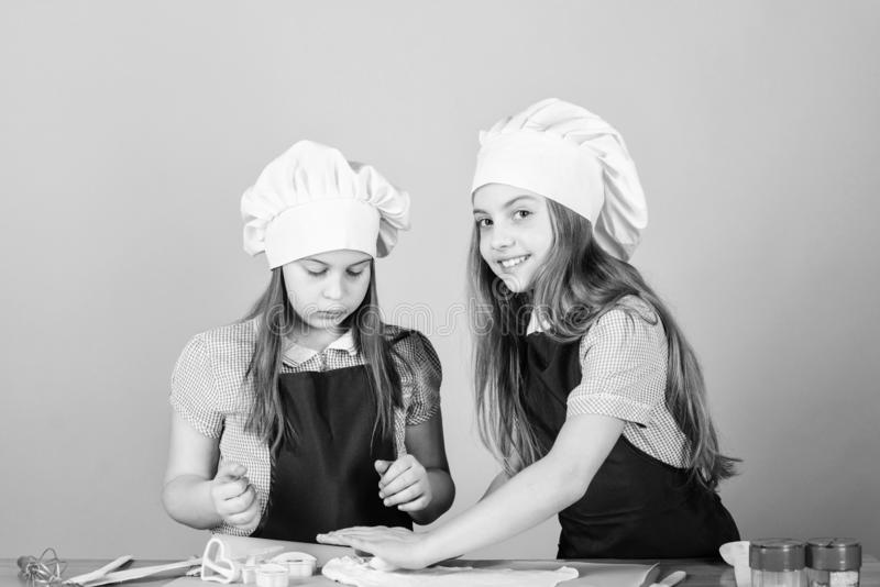 Love the smell of bread baking. Little girls baking home made pastry. Small children using flour and baking form on stock photo