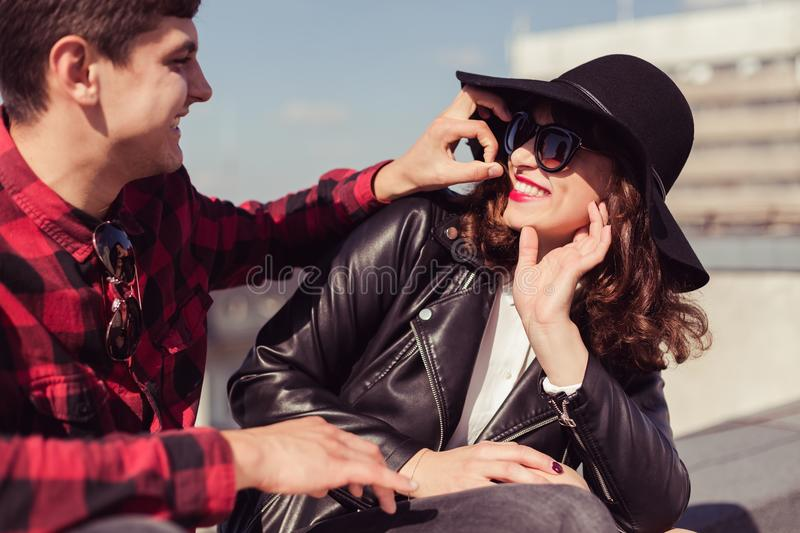 Love spending time with you. Man with checked, hipster shirt needling the women with glasses, black hat and leather jacket stock photography