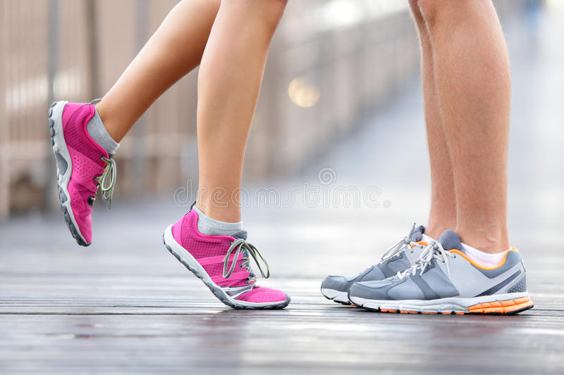 Love sport concept - running couple kissing. Closeup of running shoes and girl standing on toes to kiss boyfriend during jogging workout training outdoors on