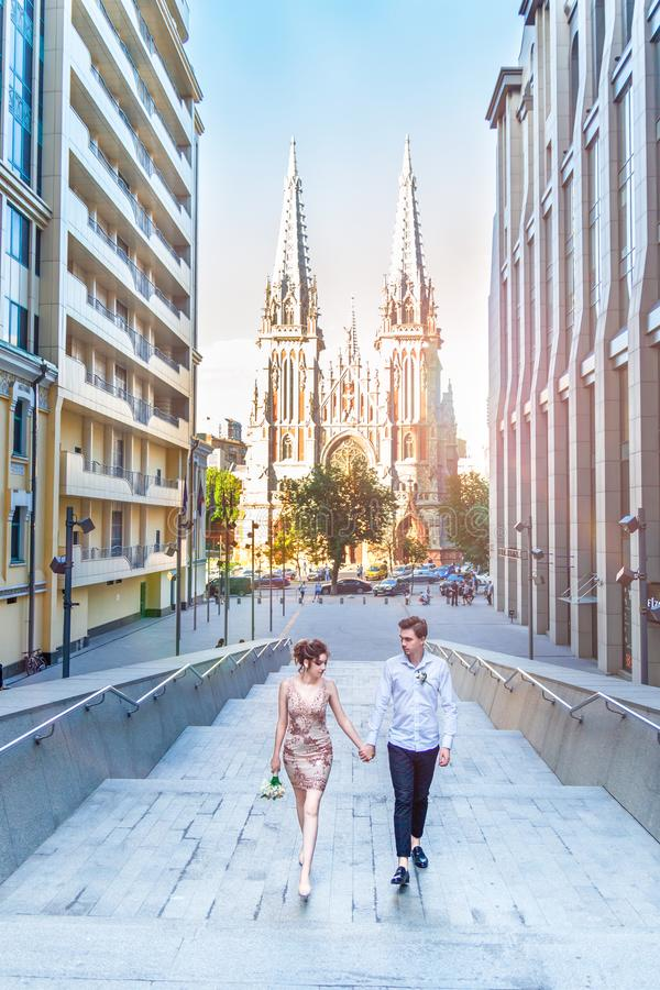 Amazing Love story of the beautiful young loving brunette man and woman, embrace on a city walk, walking at sunset under stock images
