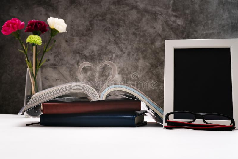 Love story book with open page of literature in heart shape and photo frame for writing space royalty free stock photos