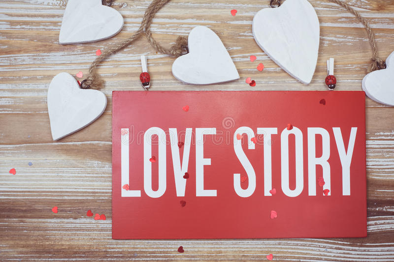 Love Story card. Love story words written on a board, vintage hearts and rustic old wooden background stock photography