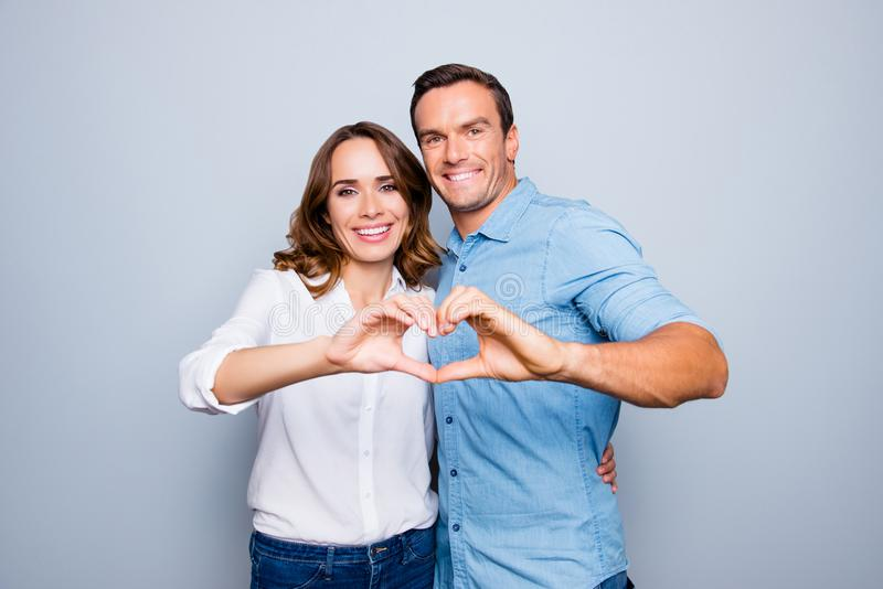 Love story of cheerful, attractive, mature, adult, lovely, cute, sweet couple in casual outfit, jeans, shirt making heart with. Fingers over grey background royalty free stock photos