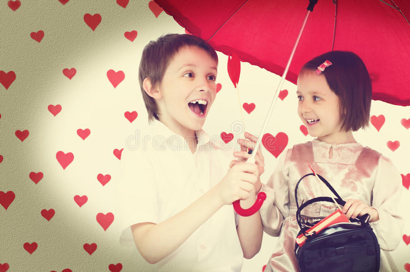 Love story. Children couple under red umbrella on hearts shapes rainy background for Valentine's Day and other occasions royalty free stock photos