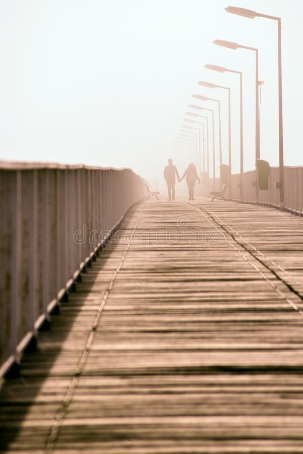 Love story of a couple on the bridge over the sea royalty free stock photography
