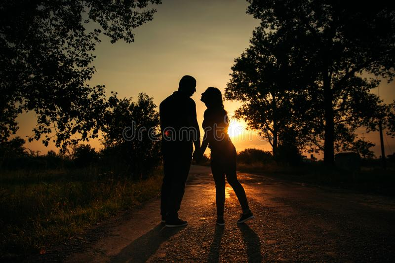 Love story. Couple on the sunset. silhouette stock images