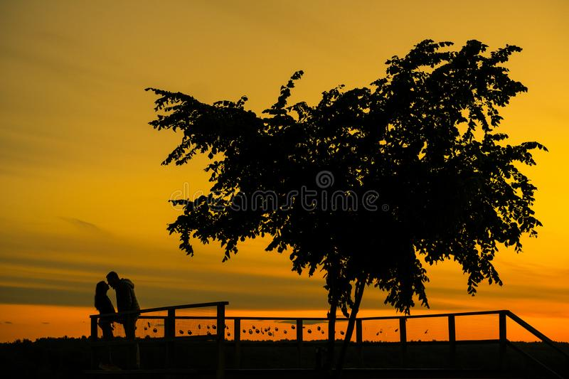 Love story. Couple on the sunset. Silhouette of Lovers stock image