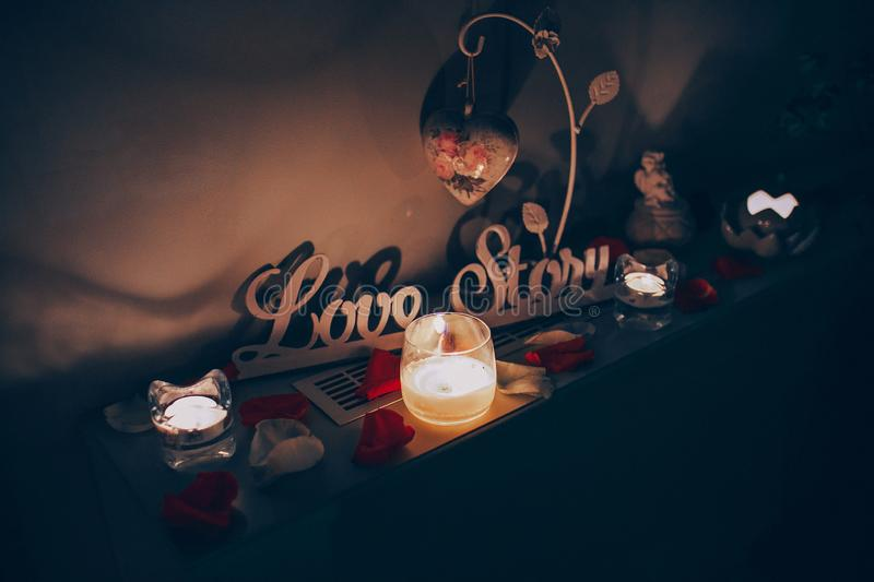 Love Story decor. Decorative element `Love Story` is decorated with candles and petals of roses at night light stock image