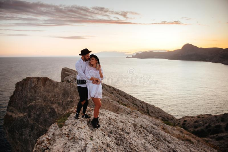 Love story on sunset. Romantic summer love story on a sunset in mountains. Young girl and boy in love royalty free stock image