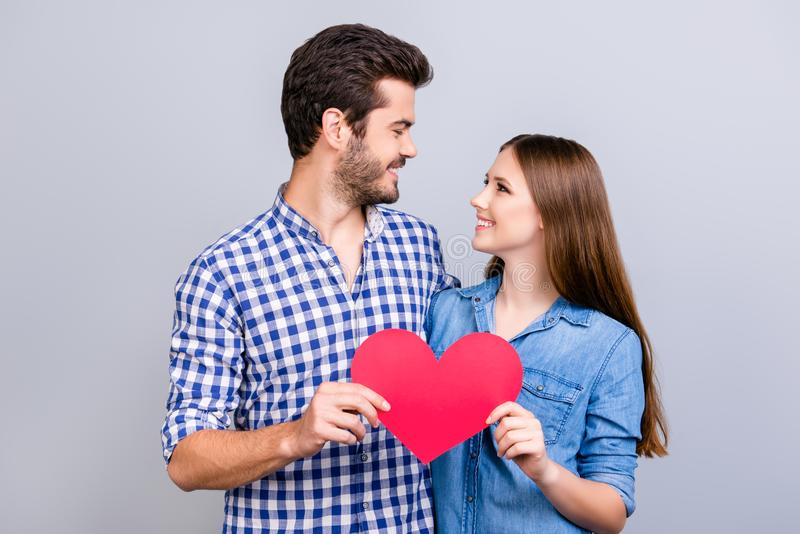Love story. Trust and feelings, emotions and joy. Happy young lovely couple in love is posing, wearing casual shirts, holding big. Red paper heart and smiling stock photos