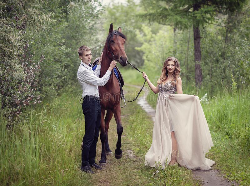 Love story. Two lovers in the forest. Photo with a horse. Love story. Two lovers in the forest. Photo with a bay horse royalty free stock photos