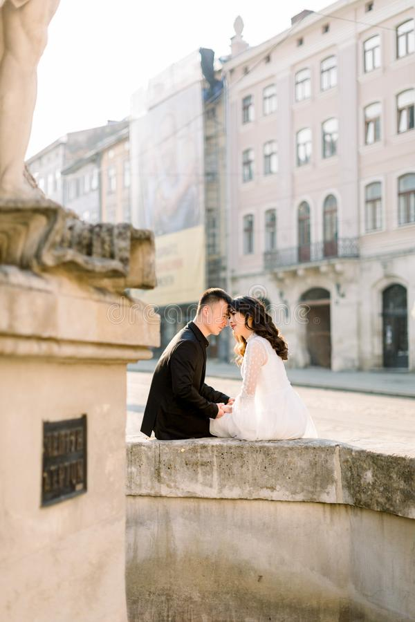 Love story or wedding shoot of young Asian couple in old city center, sitting on the old fountain, morning, summer time. Love story or wedding shoot of young stock photo
