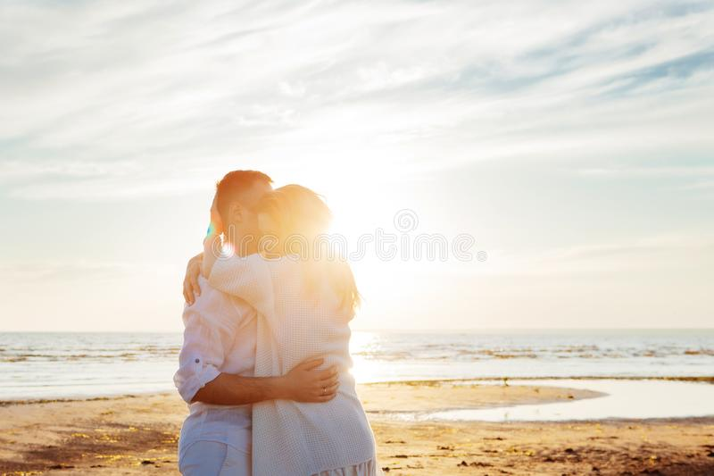 Love, sunset, romance. A young couple in long white soft clothes hugging against the backdrop of a calm sea, sunset. stock image