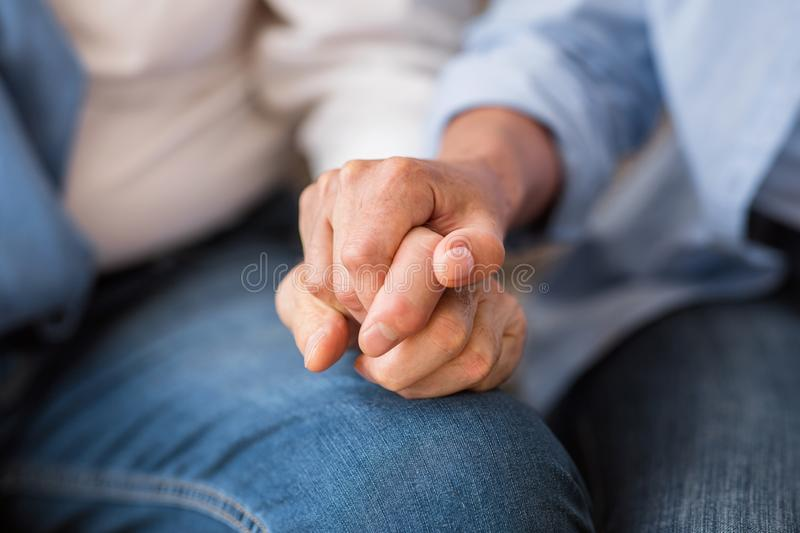 Love and support concept. Senior couple tenderly holding hands stock images