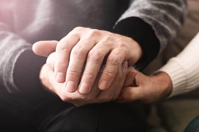 Love and support. Elderly people tenderly hold hands stock photos
