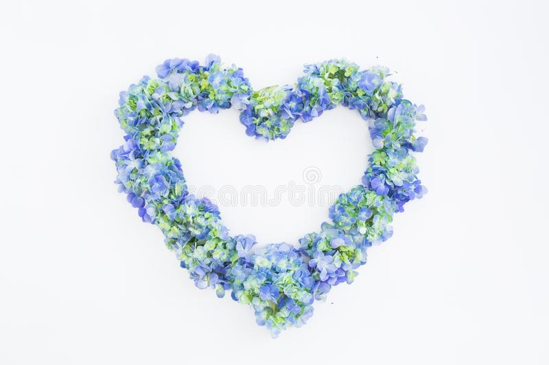 Love symbol of blue hydrangea flowers on white background. Valentines day. Flat lay, top view royalty free stock photo