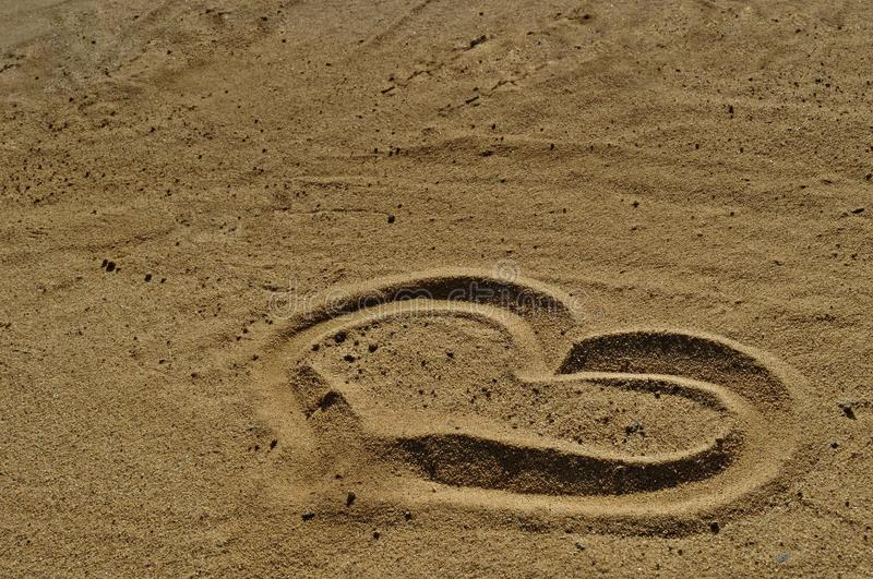 Love symbol drawn in the sand royalty free stock photography