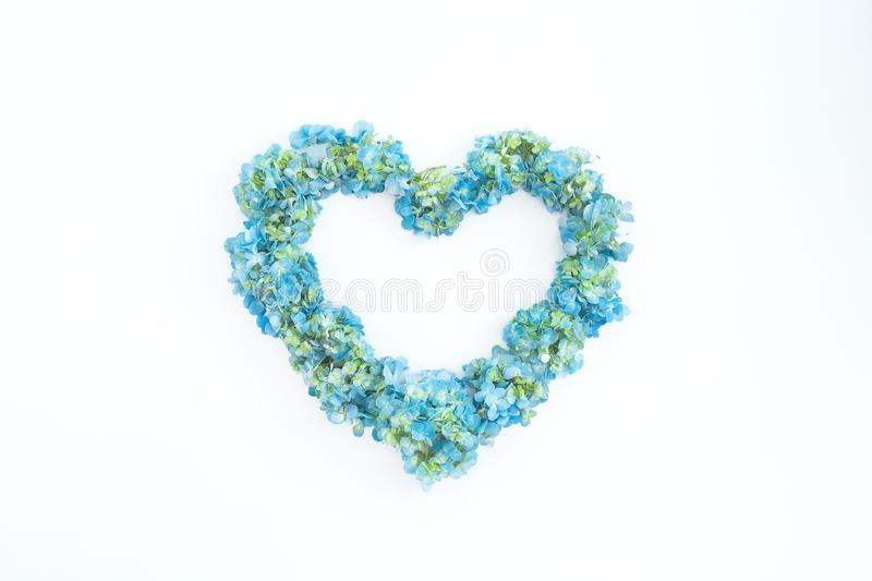 Love symbol made of hydrangea flowers on white background. Flat lay, top view. Valentines day symbol royalty free stock image