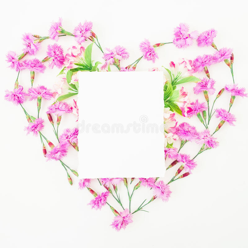 Love symbol made of pink flowers and card on white background. Flat lay, top view. stock photo