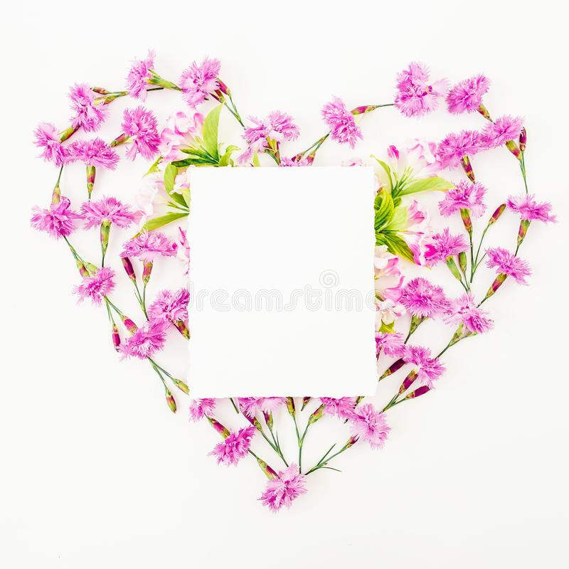 Love symbol made of pink flowers and card on white background. Flat lay, top view. Heart with paper card royalty free stock image