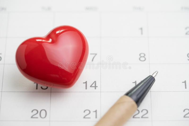 Love symbol or romance of valentine`s day concept with shiny red lovely heart shape with pen on 14 Feb white clean calendar royalty free stock photos
