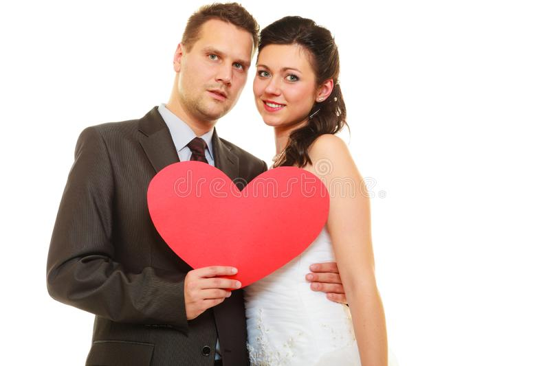 Groom and bride couple holding heart stock photo