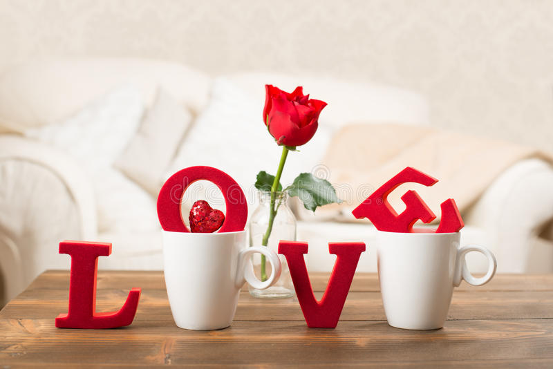 Love With Teacups. Red love letters in teacups with red rose in vase for Valentine's Day royalty free stock photography