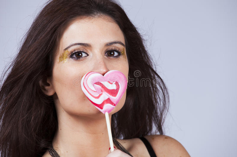 Love temptation. Beautiful woman holding a heart shape candy stock image