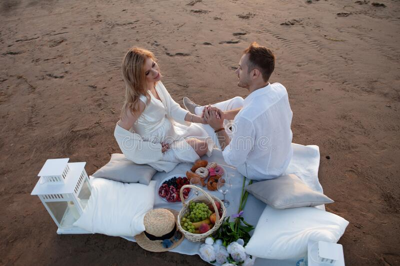 Love, tenderness. A man and a pregnant woman had a picnic on the sand with pillows, a lantern, fruit and sweet pastries. stock photography