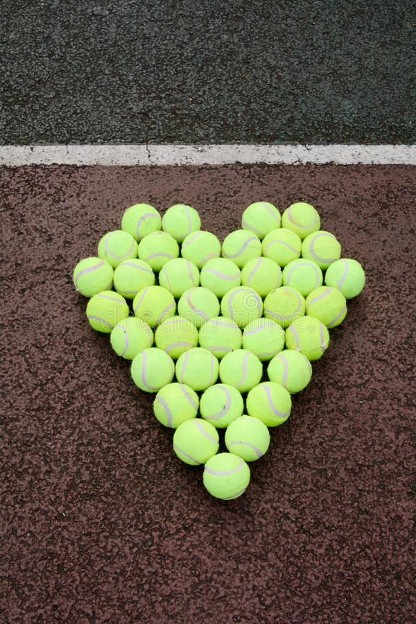 Love tennis. Portrayed using tennis balls on a hard court surface royalty free stock photography