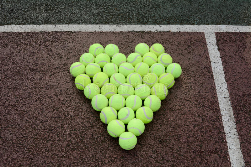 Love tennis. Portrayed using tennis balls on a hard court surface stock photography