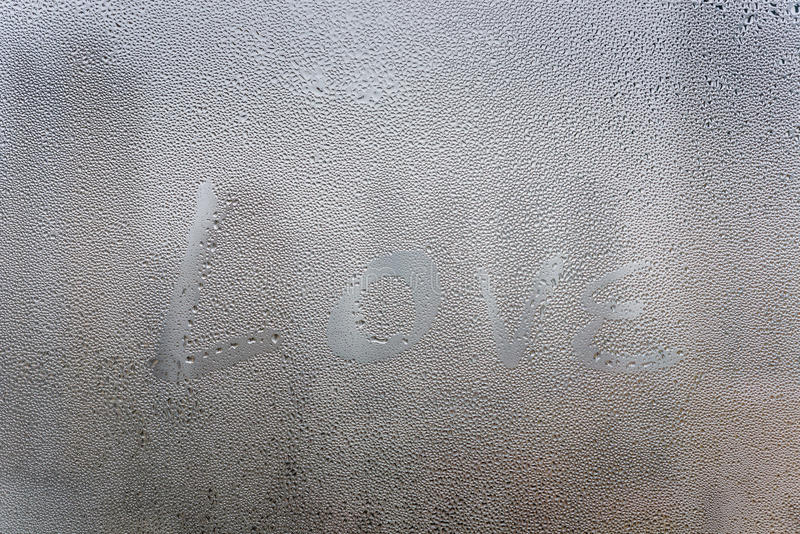 Love text draw on surface of window. In citysacpe view stock image